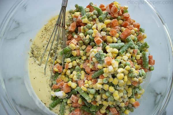 whisking frozen peas, corn, carrots, and green beans into soup mixture