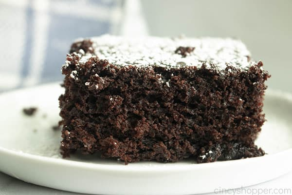 slice of chocolate cake with powdered sugar on top, sitting on a plate