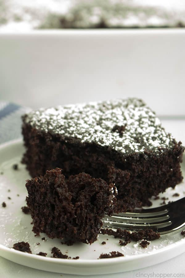 slice of rich chocolate cake on a plate, with piece on a fork