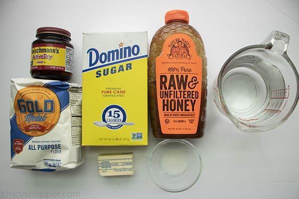 ingredients to make homemade bread - flour, sugar, yeast, honey, butter, water