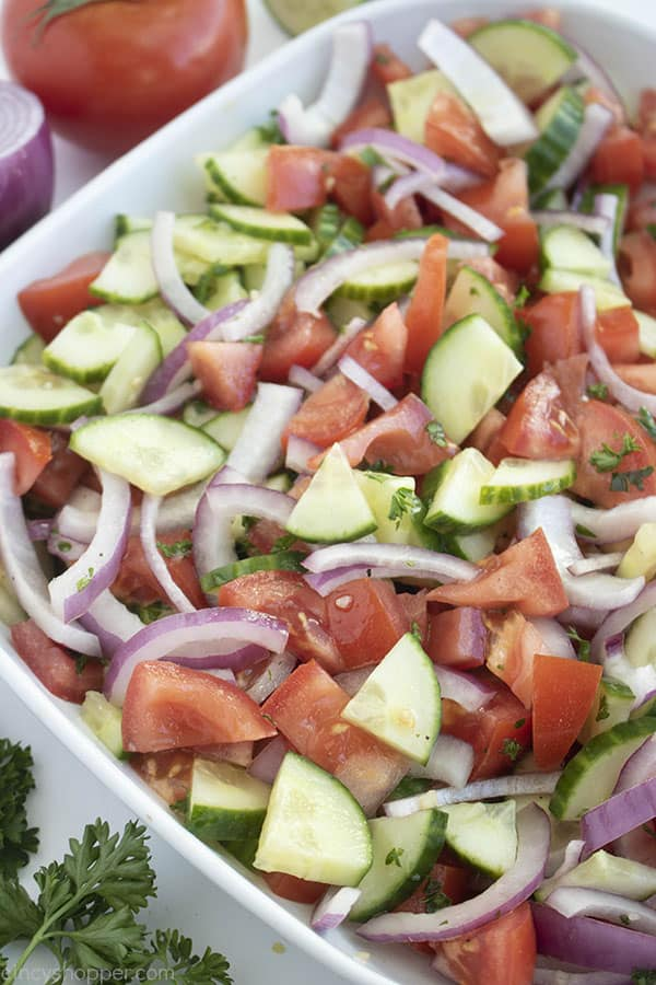 cucumber tomato onion salad in a white bowl