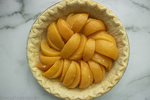 Canned peaches layered in pre-baked pie crust