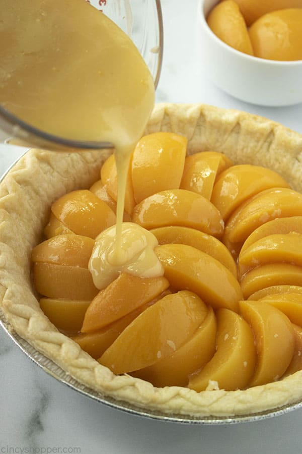 Pouring custard mixture over peaches in a pie crust
