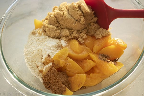 Sugar, flour, cinnamon, nutmeg and peaches in a mixing bowl