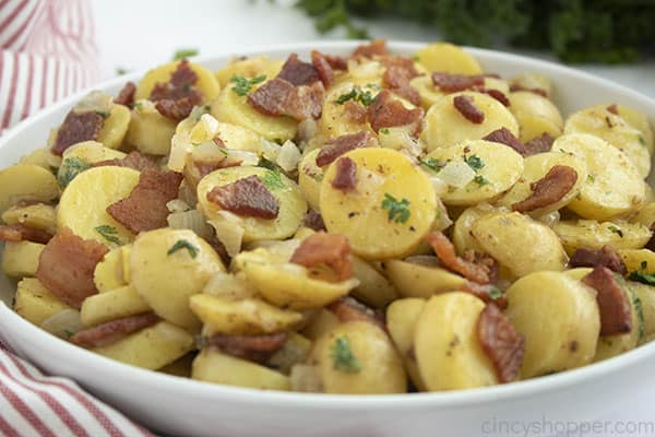 Bowl of warm potato salad with bacon with a striped dish towel