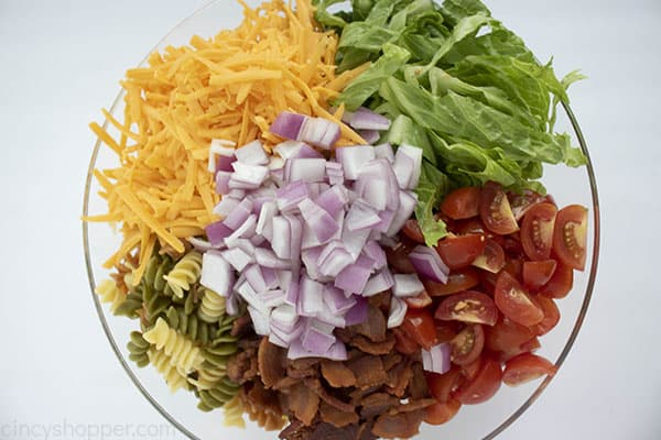 Cooked pasta, shredded cheese, lettuce, tomatoes, bacon, and red onion in a bowl