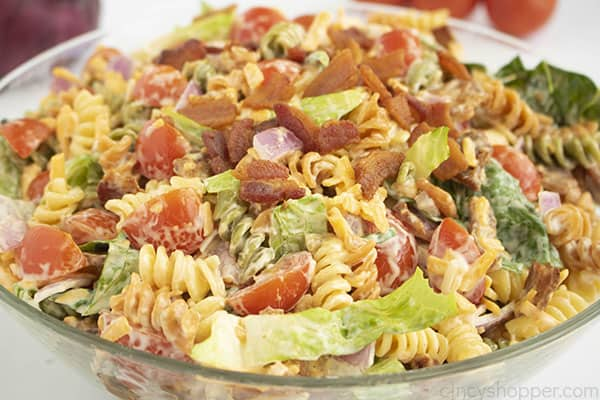 A clear bowl of salad with pasta in front of red onion and tomatoes