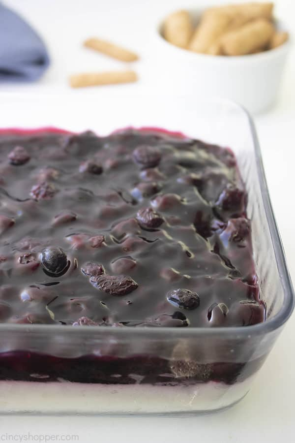 Layered Blueberry Cheesecake Dip in a clear dish on white background with graham crackers in background