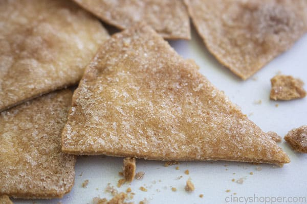 Baked cinnamon chips on white background with crumbs