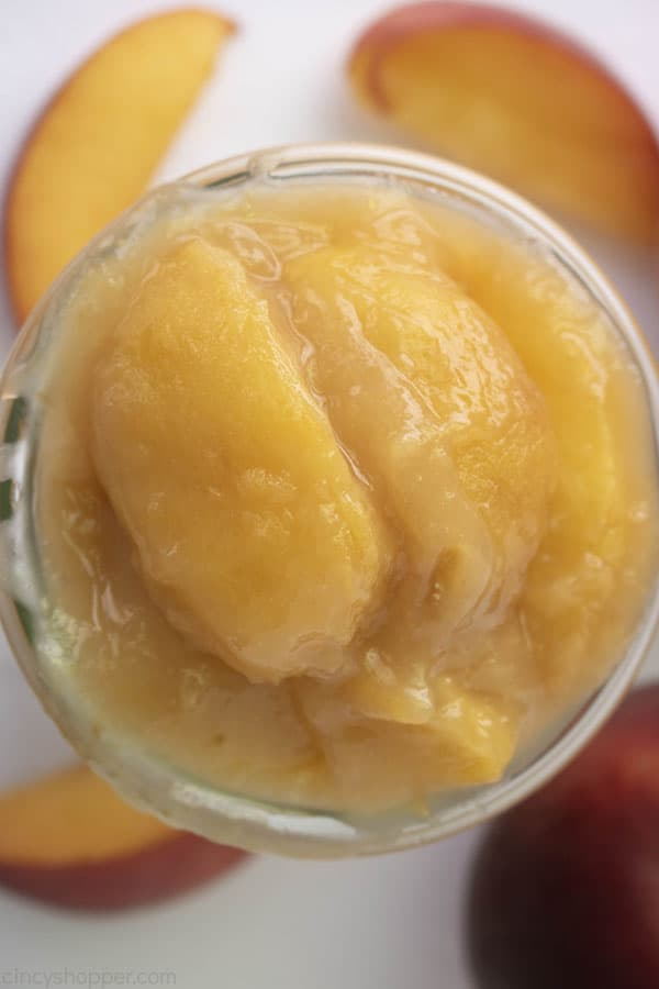 Overhead shot of fresh homemade peach filling in a glass jar on white background