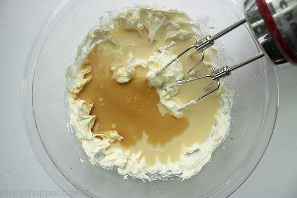 Cream cheese, condensed milk and vanilla in a clear mixing bowl with hand mixer