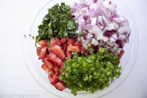 Diced and chopped ingredients for fruit salsa laid next to each other in clear mixing bowl
