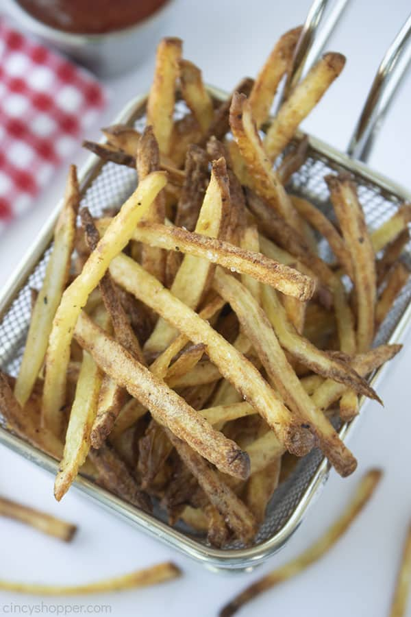 Air Fryer French Fries in a basket with white background with ketchup and a red and white checkered napkin