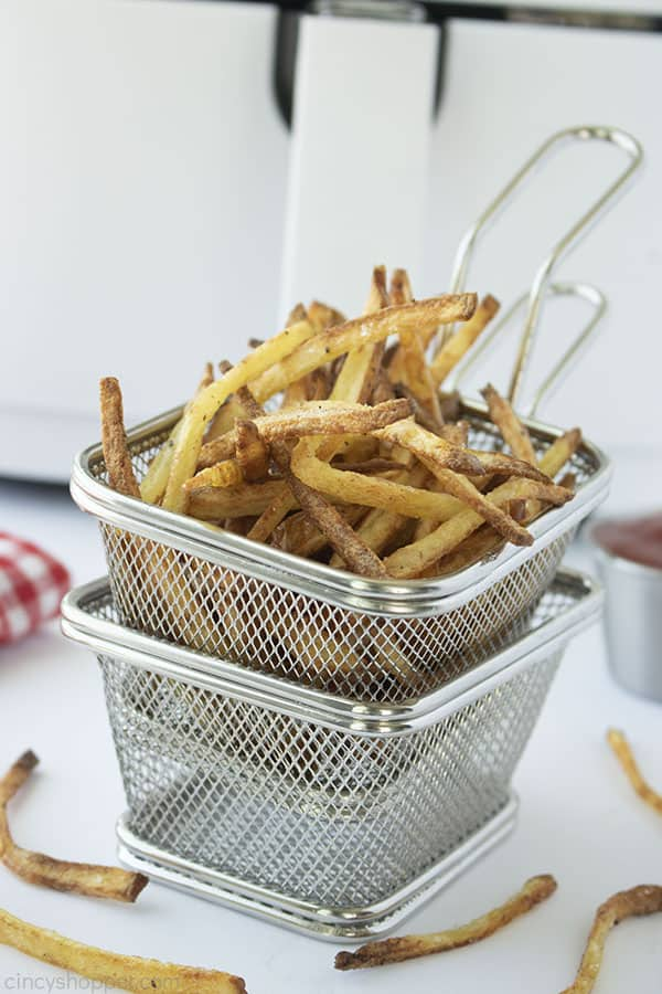 Homemade French Fries in a stainless basket with air fryer in background
