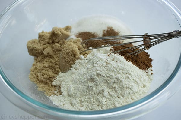 dry ingredients for the crisp topping in a large clear mixing bowl and an whisk on the right side of the bowl