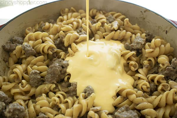 Image of the Macaroni Hamburger Helper with the Cheese Sauce being poured over in a large cast iron skillet