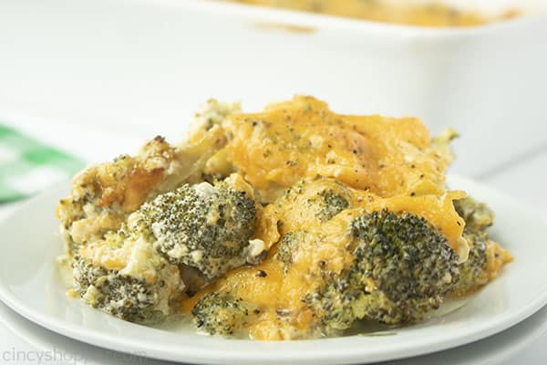 Cheesy Broccoli Casserole serving on a white plate with a green napkin and casserole dish in background