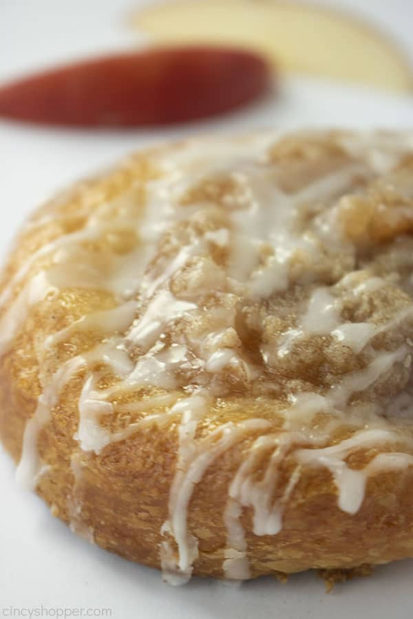 Closeup of the side of crumb topped apple danish with a white background.