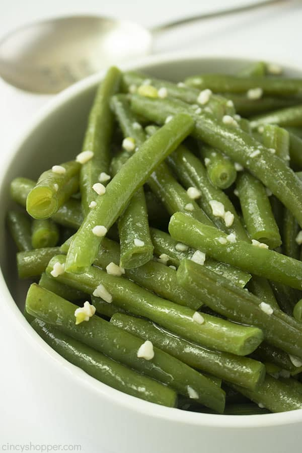 Garlic Green Beans in a white bowl with white background and spoon in th eback