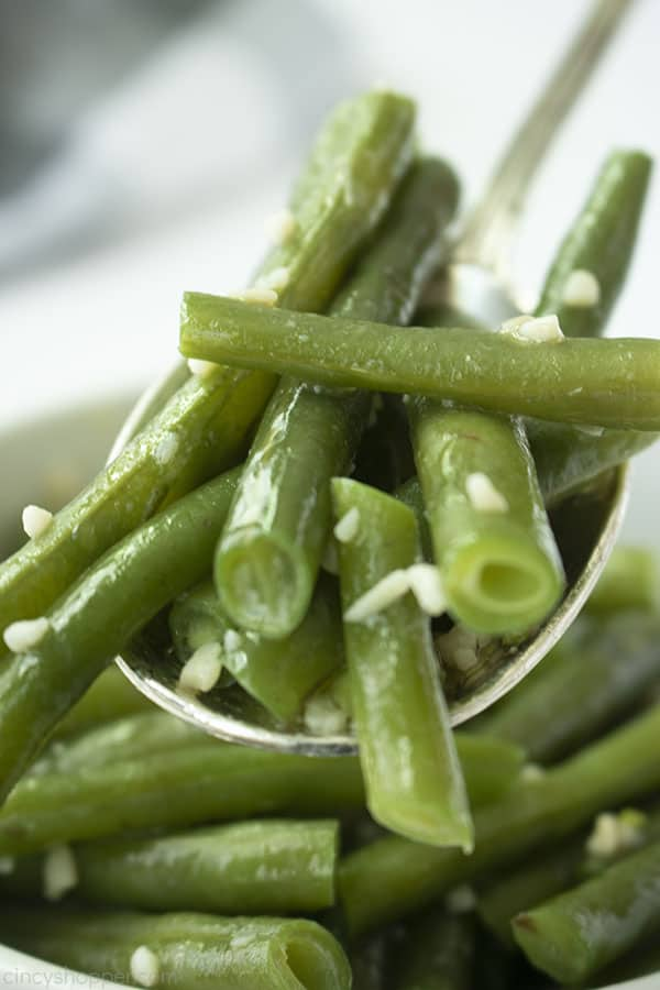 Spoon filled with fresh garlic green beans with butter