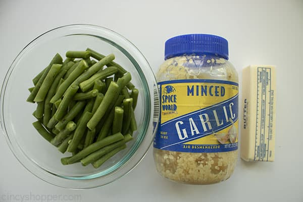Ingredients to make buttery garlic Green Beans - clear bowl fresh green beans, jar of garlic and stick of butter.