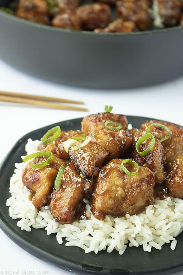 General Tso's Chicken on a black plate with rice and pan in back on a white background