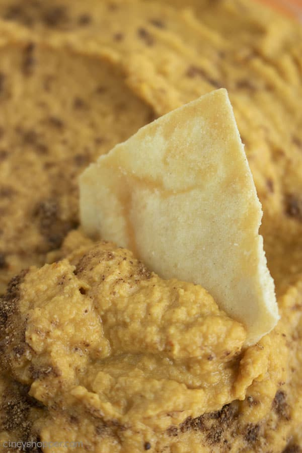 Closeup of Pita Chip dipped inside of Pumpkin Hummus.