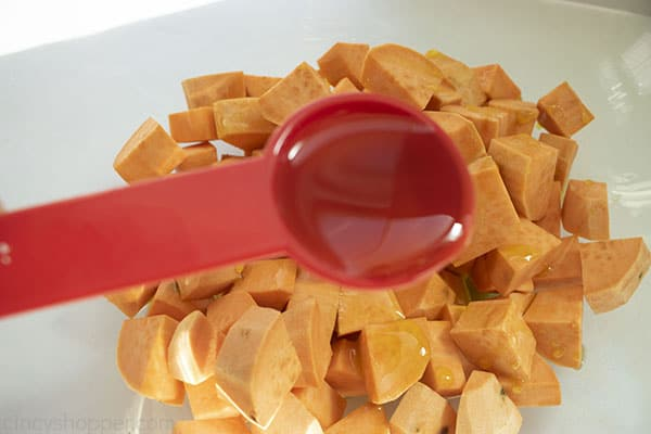 Measuring spoon filled with olive oil pouring on diced sweet potatoes in clear bowl.