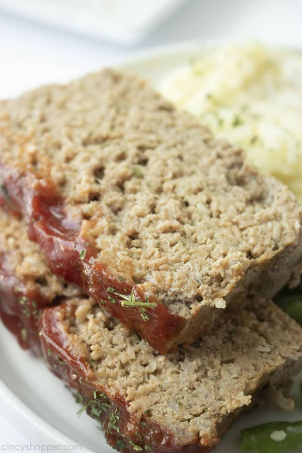 Closeup of meatloaf slices on a white plate with mashed potatoes