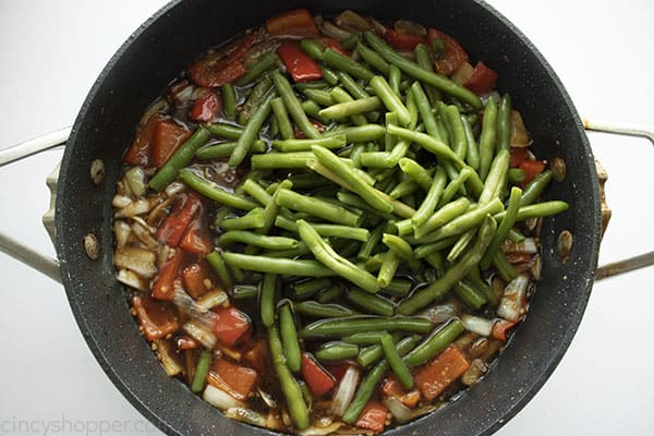 Overhead image of green beans being added into the mixture for the Mongolian Beef recipe cooking in a black skillet