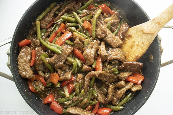 Image of the fully cooked Mongolian Beef recipe in a large black skillet with a wooden spatula on the right hand side