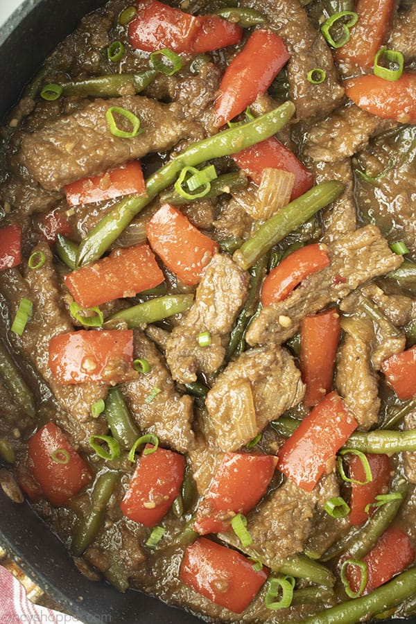 Image of Mongolian Beef with red peppers and greens beans in a black skillet