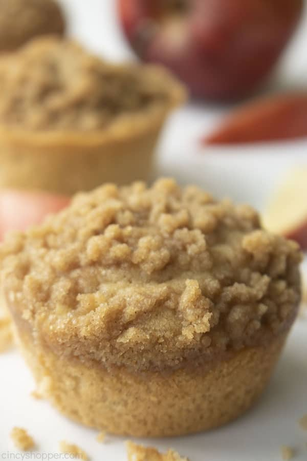 Apple Muffins with crumb topping on a white board with red apple and slices in background