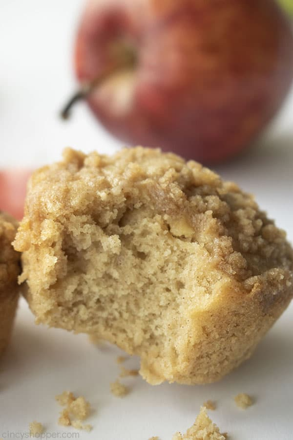 Bite out of crumb muffin on a white background and red apple in the back