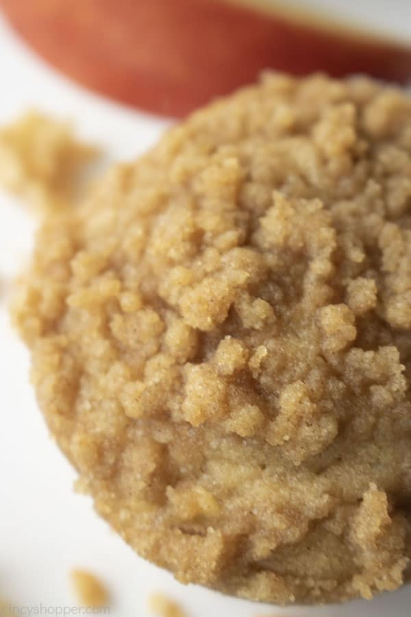 Overhead closeup of apple muffins with crumbs and apple slice