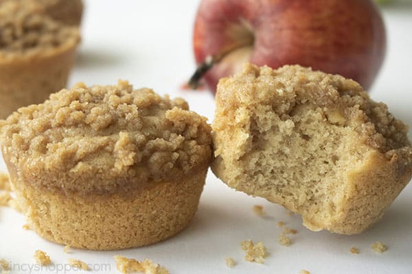Two muffins with crumbs and apple in the background