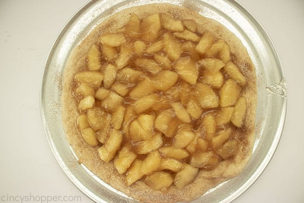 Apple pie filling on a prepared pizza crust on a pan with white bakground