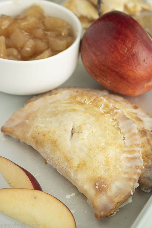 Apple Hand Pies on a pan with apple slices, red apple and bowl of apple pie filling.