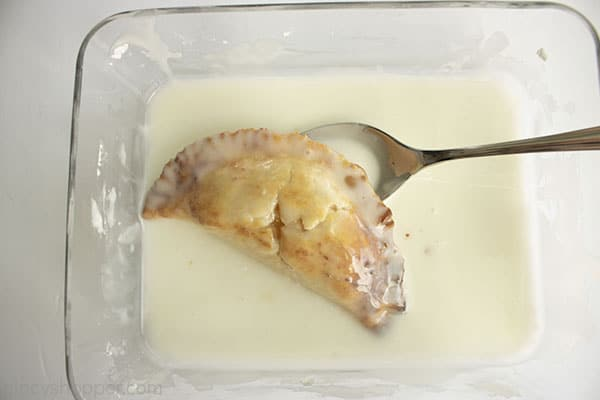 Hand pie in a clear dish with a spoon and glaze