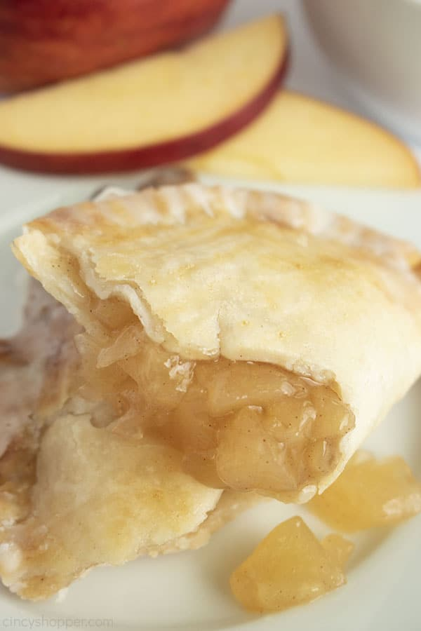 Opened apple pie with filling showing apple slices in background
