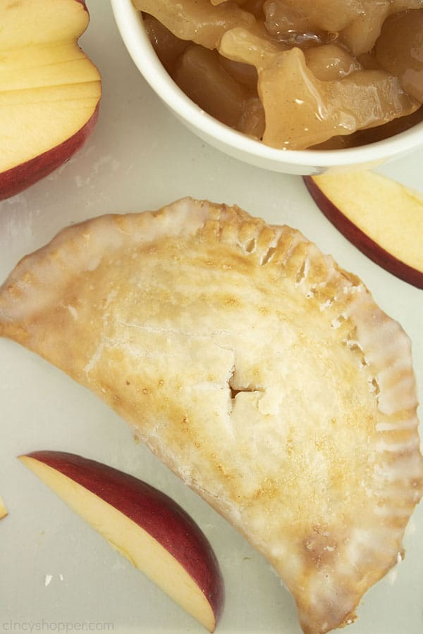 Overhead shot of one apple hand pie with apple slices and apple pie filling in a whit ebowl