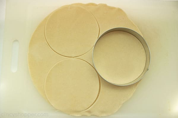 Dough on a white cutting board with round dough cutter