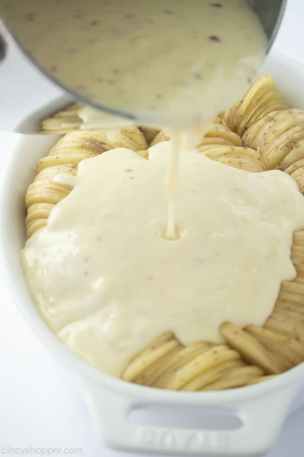 Cheese sauce pouring on sliced potatoes.