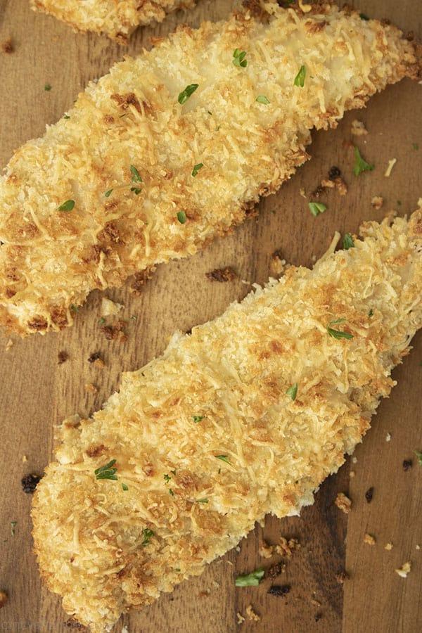 baked chicken tenders on a dark cutting board