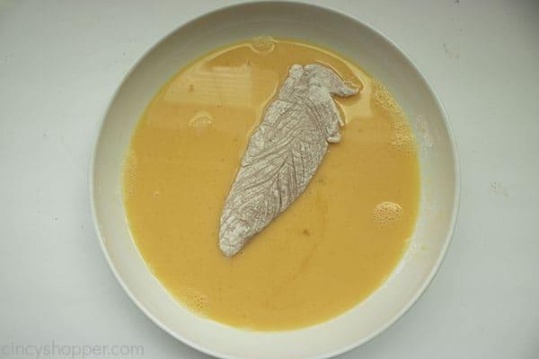 chicken tender dredging in egg mixture white bowl