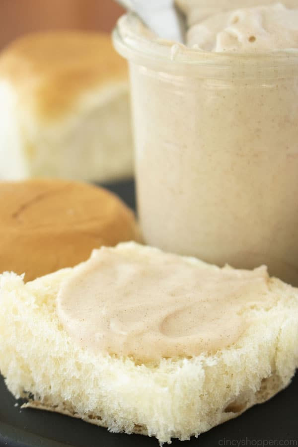 Cinnamon Butter spread on a roll. Jar and rolls in the background