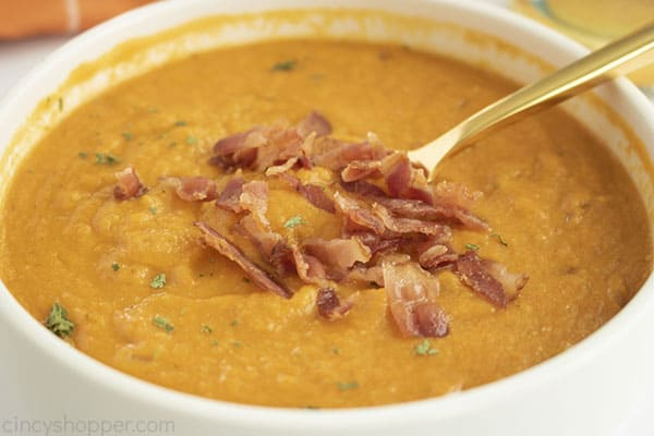 White bowl with soup with bacon topping spoon off to side