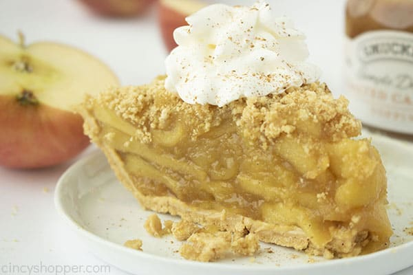 Finished apple pie slice with whipped cream. Apples and caramel in the background.