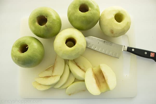 Cored and peeled green apples on a white cutting board with knife.