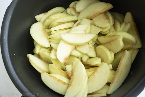 Sliced apples in a dark pot.